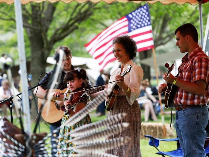 Kitty McIntyre of Mt Healthy, center, look on as Eddie Cookingham of Carthage, Eleanor Steele of Hebron and Casey Celender of Reading perform at the 45th Appalachian Festival at Coney Island.  The Enquirer/Jeff Swinger