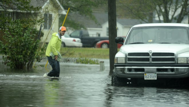 An unidentified man walks through flood waters to a truck waiting for him in Sanford, Va. on Tuesday, Oct. 30, 2012. Nearby Saxis Island was evacuated by the Virginia National Guard early Tuesday morning because of flooding by Hurricane Sandy.