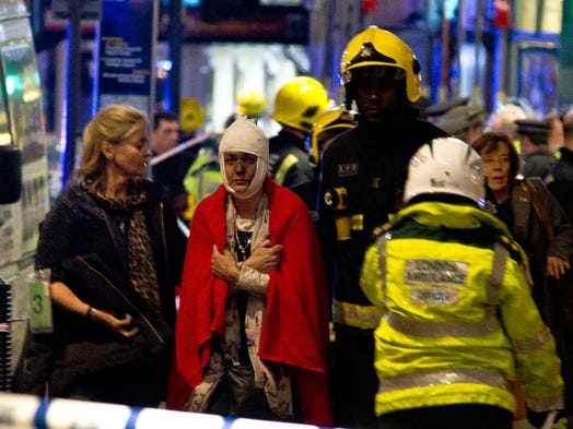 "A woman stands bandaged and wearing a blanket  given by emergency services  following an incident at the Apollo Theatre, in London during a performance at the height of the Christmas season. It wasn't immediately clear if the roof, ceiling or balcony had collapsed  during a performance. Police said they ""are aware of a number of casualties,"" but had no further details."