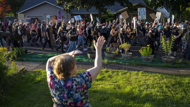 Rita Castillo of Springfield waves to Black Lives Matter marchers as they pass her home in Springfield on Friday evening. [Chris Pietsch/The Register-Guard] - registerguard.com