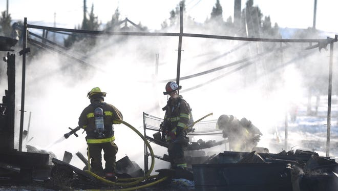 Crews work to extinguish a fire near County Road 3562 in Flora Vista on Tuesday.