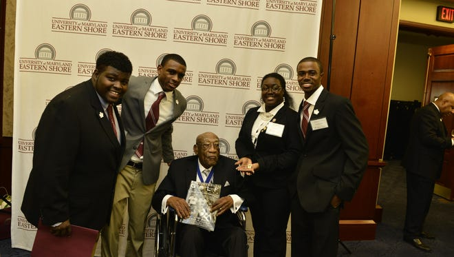 Left to right are UMES students Anthony Ward, Norman Blanco, Tiana Jones and Patrick Harris. Seated is the late Charlie Sifford at the reception the school held in his honor.