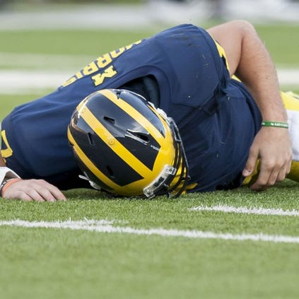 Michigan quarterback Shane Morris lays on the ground after being tackled by Minnesota defensive lineman Theiren Cockran in the fourth quarter on Saturday