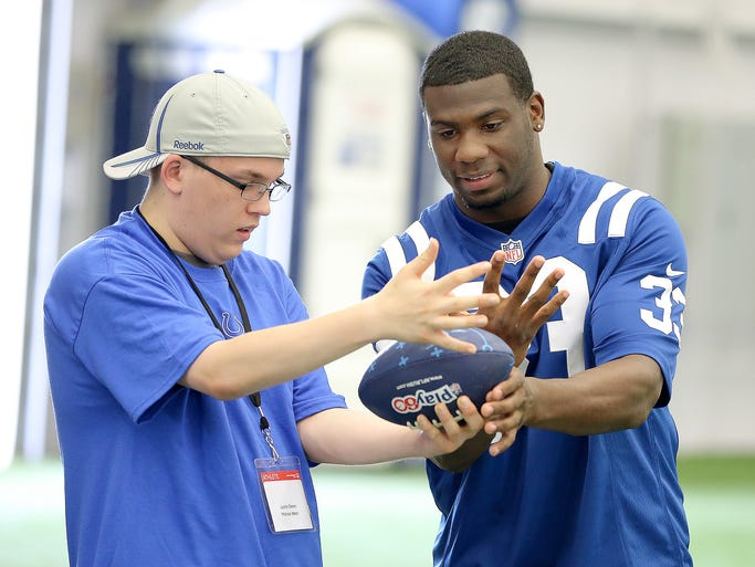 The Indianapolis Colts and Special Olympics hosted a PLAY 60 youth football camp at the Colts complex. Here Colts RB Vick Ballard shows Justin Deem, from Marion West, how to hang onto the football. Matt Kryger / The Star