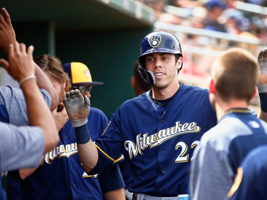 FILE - In this March 16, 2018, file photo, Milwaukee Brewers' Christian Yelich gets high-fives from teammates after scoring a run against the Cincinnati Reds during the third inning of a spring training baseball game in Goodyear, Ariz. Outfielders Lorenzo Cain and Christian Yelich are just as capable of changing games with their gloves. The two big offseason acquisitions make their Brewers debut when Milwaukee visits the San Diego Padres for their season opener on March 29.  (AP Photo/Ross D. Franklin, File)