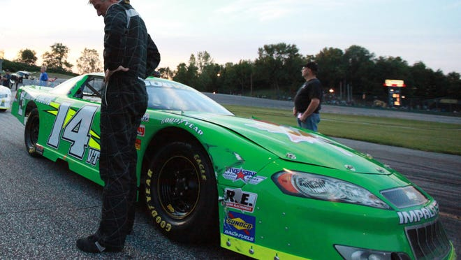 Phil Scott waits by his stock car before the start of the Charter Communications Late Model Race at Thunder Road International Speedway in Barre on July 7, 2011.