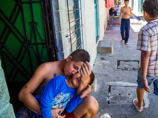 Alfredo Contreras holds his son, Jesus, 6, in a neighborhood controlled by gangs in San Salvador, El Salvador June 18, 2014. Poverty and violence has been sending many Central Americans up to the U.S. in increasing numbers.