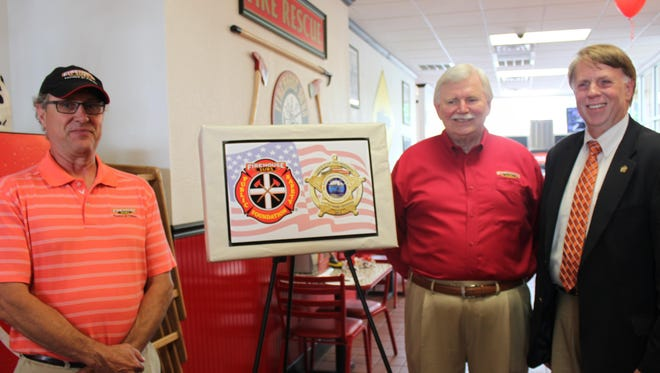 David Whidden, franchise owner, Jim Maxwell, area representative for Firehouse Subs, and Sheriff John Mehr pose during a press conference Thursday.