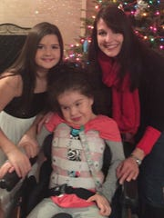 Bridget Feeney, her sister Brianna and their mother, Patti ,pos in front of the family Christmas tree.