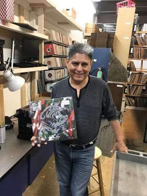 "All That Music owner George Reynoso holds a limited-edition Cure album. ""It appears the generation that has grown up with music on telephones and streaming is now appreciating the physical form of all the giants,"" he says."
