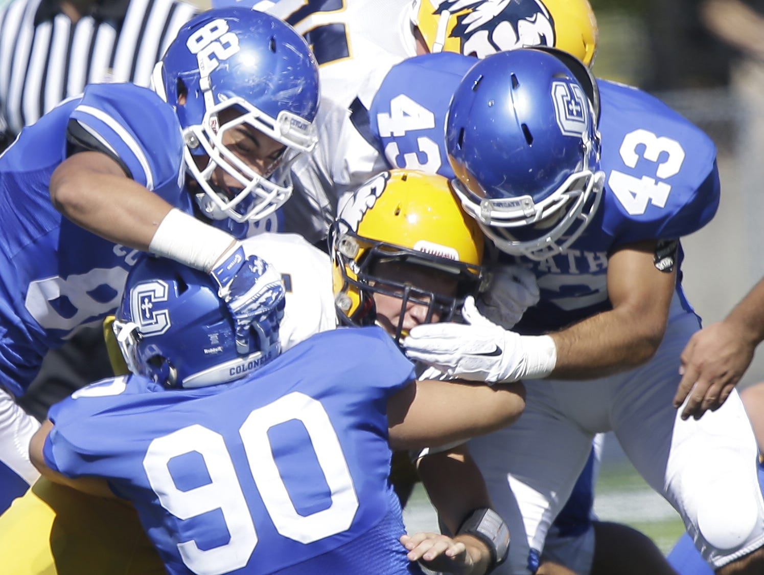 Grant County's Nick Stephenson (5) is tackled by several Covington Catholic defenders during their football game Saturday.