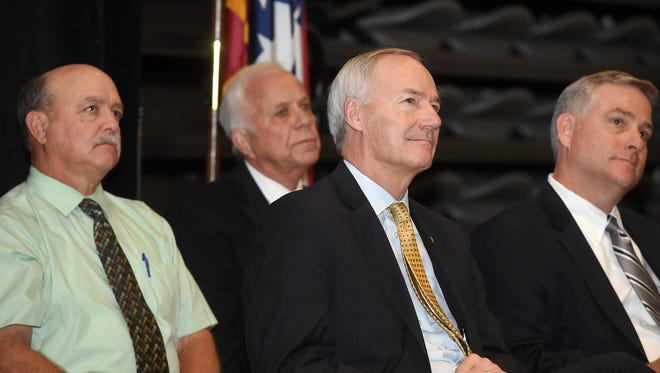 Gov. Asa Hutchinson, third from left,  listens to a speaker at Arkansas State University Mountain Home on Thursday, Oct. 15, 2015. Hutchinson was on hand for the announcement of 225 new jobs at Baxter International in Mountain Home.