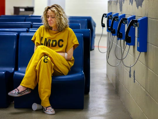 Christi Embry sits in Metro Corrections booking area