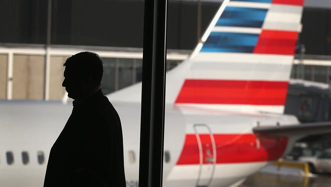An American Airlines jet with the company's new tail logo sits at a gate at Chicago's O'Hare Airport Dec. 9.  American has completed a merger deal with US Airways. The deal will make American Airlines the world's largest airline, flying about 6,700 flights per day.