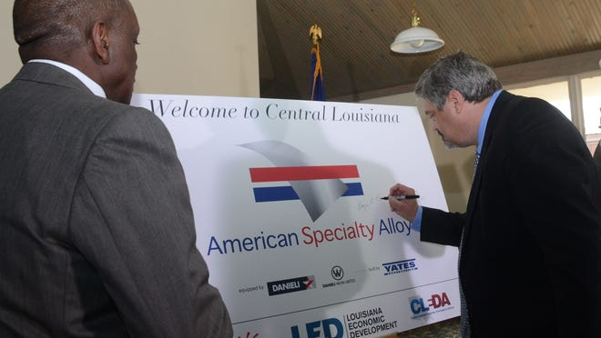 Roger Boggs (right), founder and chief executive officer of American Specialty Alloys, puts his signature on a sign at an event Wednesday celebrating a $2.4 billion aluminum manufacturing complex in Pineville.