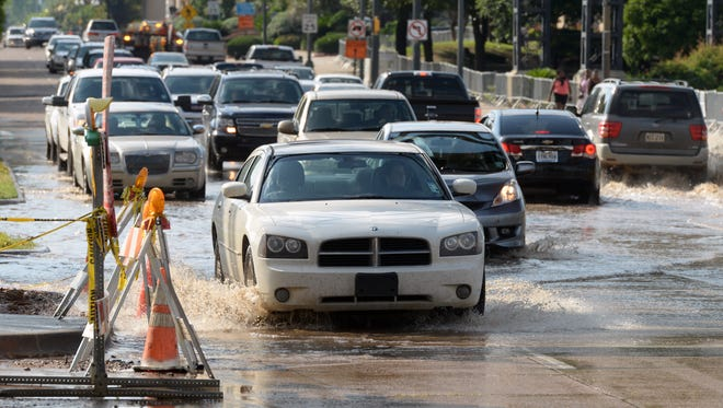Motorists push through rising waters from drainage located on the Clyde Fant Parkway in front of River View Park. The Clyde Fant will be closed beginning at 7 pm Thursday and will remain closed for several days in that area.