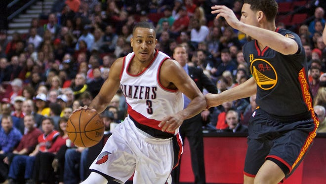Portland Trail Blazers guard C.J. McCollum dribbles around Golden State Warriors guard Klay Thompson during the second half of an NBA basketball game in Portland, Ore., Friday, Feb. 19, 2016.