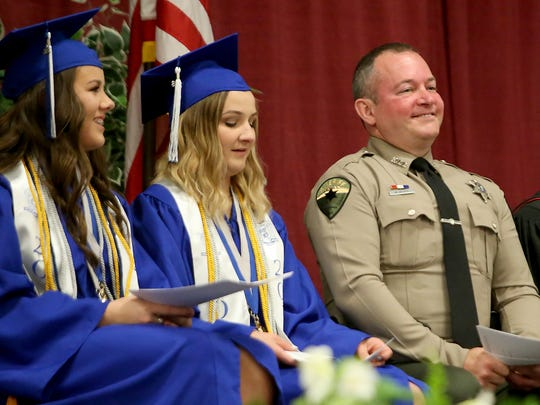 School resource officer Sheriff Deputy Mark McVey (right) smiles from his seat on the stage as the Olympic High School Class of 2018 graduation ceremony begins at the Kitsap Sun Pavilion on Thursday, June 14, 2018.