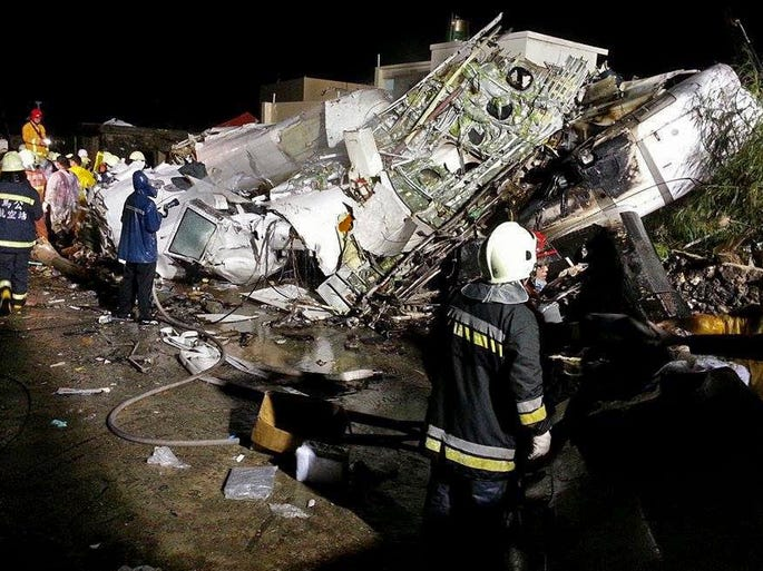 Rescue workers survey the wreckage of TransAsia Airways Flight GE222 that  crashed while attempting to land in stormy weather on the Taiwanese island of Penghu on July 23, 2014.