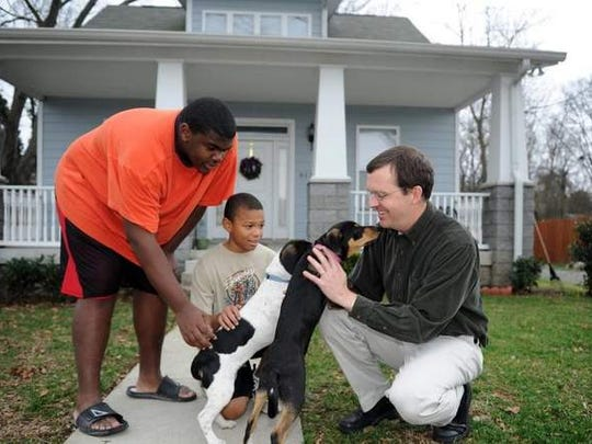 Brant Bousquet, executive director of Hard Bargain Mt. Hope Redevelopment, plays with Isiah and Donovan Gentry's new puppies in front of their home built by the nonprofit.