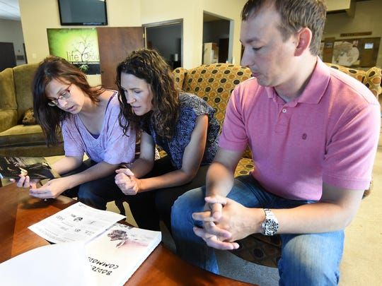 Sabrena Klausman, from left, Gretchen Smeltzer and Chris Carter look over material on sex trafficking. The three have started a nonprofit organization, Into the Light, with a mission to provide refuge and restoration to underage female victims of sexual exploitation. The group hopes to establish a residential group home for girls who have been trafficked.
