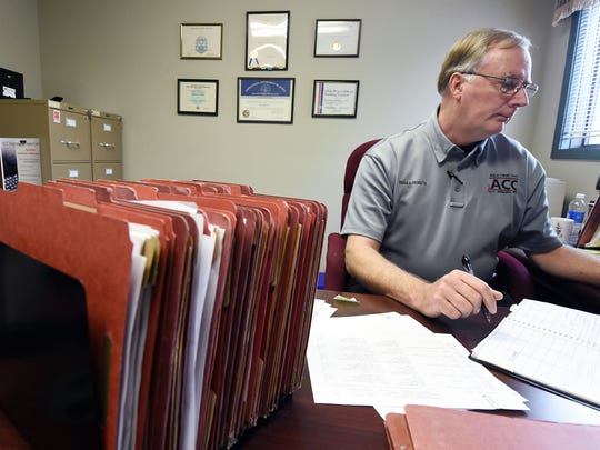 Parole officer Harry Nuccio works on one of his 160 parolee cases Wednesday. Nuccio said an average caseload would be about 75 parolees. He has had as many as 400 parolees in a year period.