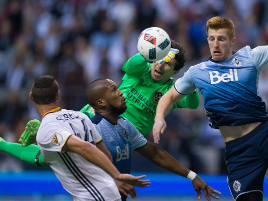 Los Angeles Galaxy goalkeeper Brian Rowe, srear, knocks the ball down with his hands as Vancouver Whitecaps' Tim Parker, right, tries to get his head on it in front of teammate Kendall Waston, second from left, during the first half of an MLS soccer game Saturday, April 2, 2016, in Vancouver, British Columbia. (Darryl Dyck/The Canadian Press via AP)