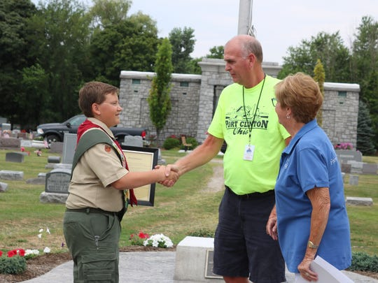 Tracy Colston, Port Clinton's cemetery sexton, and Sandra Koch, of the Friends of the Cemetery, congratulate Jayce Kennedy as he reached the rank of Eagle Scout with a project to revitalize Lakeview Cemetery's veterans' memorial.
