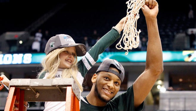 Michigan State center Adreian Payne celebrates the Big Ten tournament victory over Michigan with his friend, Lacey Holsworth, 8, from St. Johns on Sunday, March 16, 2014 at  Bankers Life Fieldhouse in Indianapolis, Indiana.
