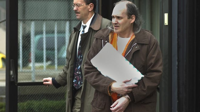 Donald Anson, in custody, leaves the federal building after a hearing on his child pornography charges.