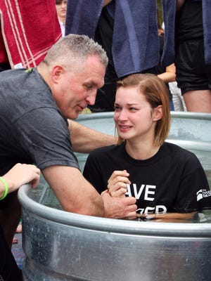 The Bridge Fellowship Lead Pastor Phil Wilson baptizes daughter SaraGrace Wilson on Sunday at an outdoor service at Charlie Daniels Park in Mt. Juliet.