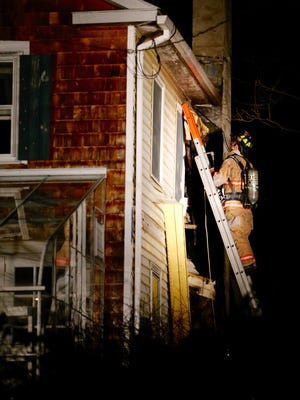 A firefighter climbs to the top level to examine damaged caused by a fire near the chimney of the home at 2 Monastery Road, in Southport, on Tuesday.