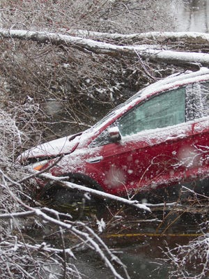 A 2014 Ford Escape slid off Norton Road into the Red Cedar River in Marion Township, one of numerous accidents due to treacherous roads Thursday, March 1, 2018.