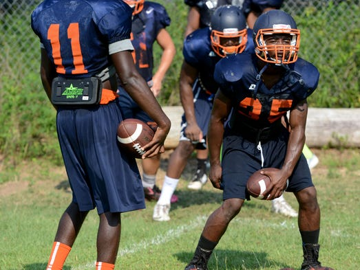 Escambia High School players work on their triple option attack Thursday while preparing for the 2014 fall season.