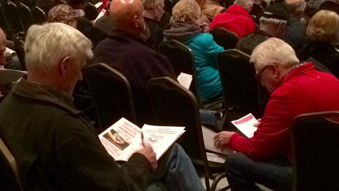 Teamsters read information about proposed cuts to their pensions during an informational meeting in Green Bay on Saturday, March 5, 2016.