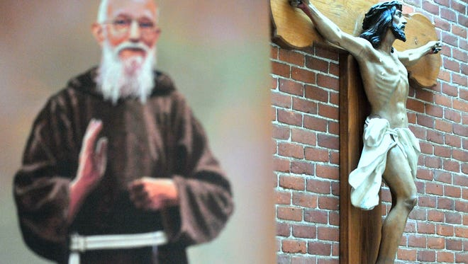 A portrait of Father Solanus Casey is displayed outside the Saint Bovaventure Chapel next to the crucifix.