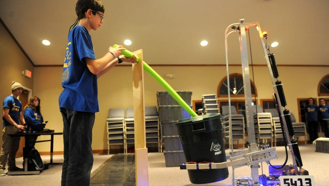 Coulter Williams feeds a prop into a recycling bin held by the robot built by the 5413 Stellar Robotics team during a presentation Tuesday evening at the Ontario Christian Church.