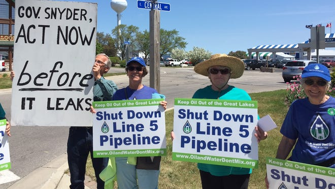 Demonstrators, including Susan Page of Straits Area Concerned Citizens for Peace Justice and the Environment (second from  right) and June Thaden of Oil and Water Don't Mix (right), carry placards against Line 5 outside the Shepler's ferry docks in Mackinaw City on Tuesday.