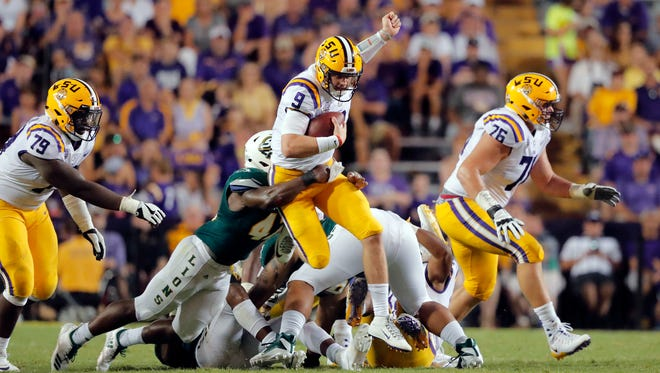 LSU quarterback Joe Burrow (9) carries as Southeastern Louisiana linebacker Tamarcus Russell tries to tackle in the second half of an NCAA college football game in Baton Rouge, La., Saturday, Sept. 8, 2018. LSU won 31-0. (AP Photo/Gerald Herbert)