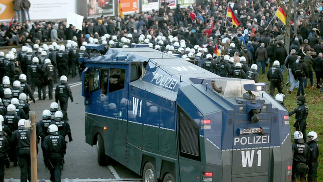 Police drive back right-wing demonstrators with a water cannon in Cologne, Germany Saturday Jan. 9,  2016. Women's rights activists, far-right demonstrators and leftwing counter-protesters all took to the streets of Cologne on Saturday in the aftermath of a string of New Year's Eve sexual assaults and robberies in Cologne blamed largely on foreigners.