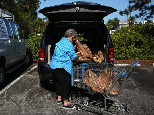Daphne Tull donates groceries at St. Matthews House on Tuesday, May 10, 2016 in Naples. Tull lost her hearing in 2011 and found new purpose in couponing for food to donate to St. Matthew's House food pantry.