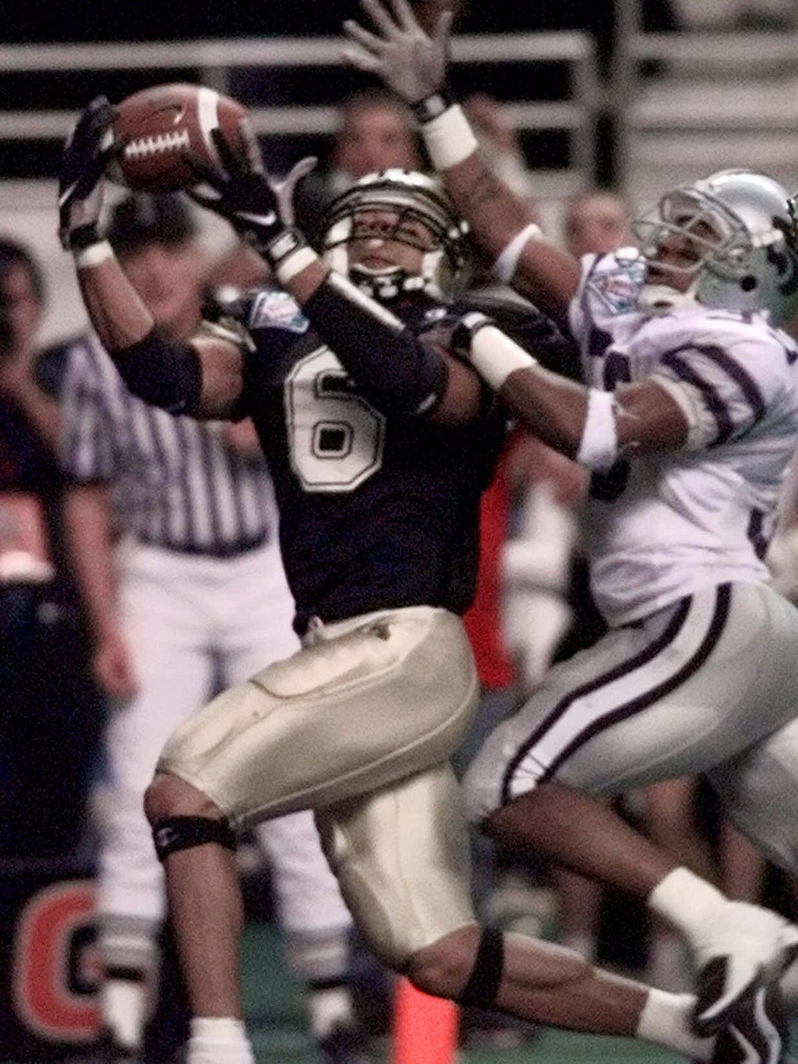 Purdue receiver Isaac Jones (6) pulls in the winning touchdown as Kansas State's Dyshod Carter (35) defends on the play during the final moments of the Alamo Bowl in San Antonio, Texas, Dec. 29, 1998. Purdue won 37-34.