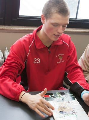 Ben Rutherford, 15, talks about why he made his stained glass mosaic while they were learning about the Holocaust in Social Studies class at St. Philip Catholic Central High School.