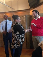 At a surprise goodbye luncheon Tuesday, North End Community Improvement Collaborative founder Deanna West-Torrence, accepts an appreciation award from Community Development Coordinator Tony Chinni, right. Col Michael J. Howard, left, vice commander of the 179th Airlift Wing, Ohio Air National Guard, will replace West-Torrence as executive director.