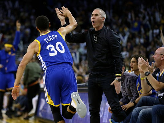 Golden State Warriors' Stephen Curry celebrates with a fan after scoring against the Washington Wizards during the second half of an NBA basketball game Sunday, April 2, 2017, in Oakland, Calif. (AP Photo/Ben Margot)