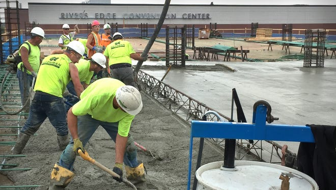 Crew members pour concrete  at the new River's Edge Convention Center parking ramp Tuesday.