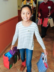 Lillyanna Martinez, 10, carries various cold-weather