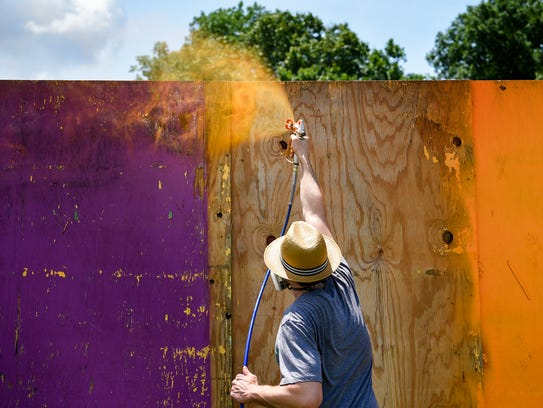Stephen LaBelle paints the walls in preparation of