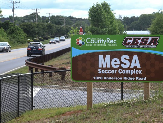 Cars drive by MeSA Soccer Complex along Anderson Ridge