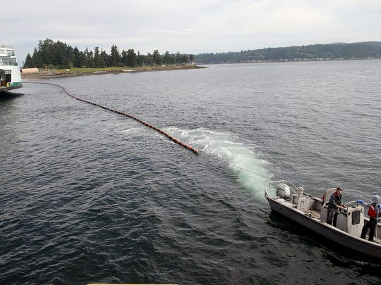 A oil safety boom is pulled into place around the Washington State ferry Chimacum at the Manchester Fuel Depot on Monday. The ferry was doing a test to see if it could be fueled there.